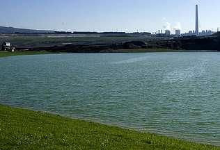 Un murallón de tierra separa las aguas del lago del centro de As Pontes, desde donde aún no es visible Autor de la imagen: | SANTI VILA