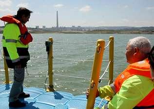 El director de la mina, de pie, revisa los controles del agua