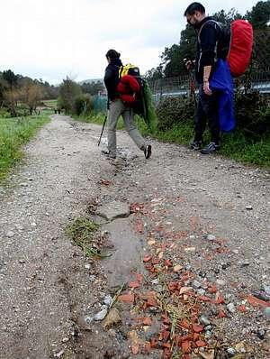 Los peregrinos tienen que sortear los baches que hay en el suelo.