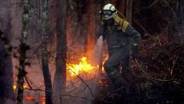 Un operario intentando apagar el fuego de la Fragas do Eume.