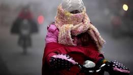Una mujer conduce una motocicleta muy abrigada para soportar el fr�o en China. FOT�GRAFO: CHINA DAILY | REUTERS