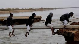 Un grupo de hombres cruza una zona inundada a trav�s de una viga en Tabuk, Arabia Saud�. FOT�GRAFO: STRINGER | Reuters