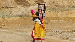 Una mujer sostiene a su hijo mientras trabaja en la construcci�n de una carretera en la India. FOT�GRAFO: RUPAK DE CHOWDHURI   REUTERS