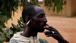 Un hombre de mali fuma un cigarrillo con otro m�s situado en su oreja.