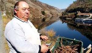 Manuel Lorenzo traballa cunhas cepas ao lado do r�o Mi�o en Belesar