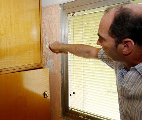 Los docentes del colegio Vicente Risco muestran el cartel que avisa de no tocar              ni abrir la ventana, as� como las humedades.