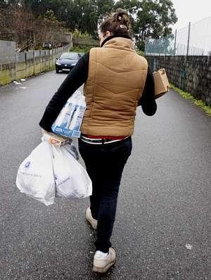Una joven vuelve a casa con la comida, mientras una mujer, en O Grove, recoge los molletes de pan.