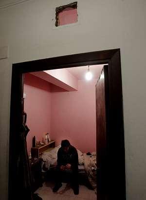 Daniel, sentado en la cama de su cuarto, por el que paga 20 euros al mes