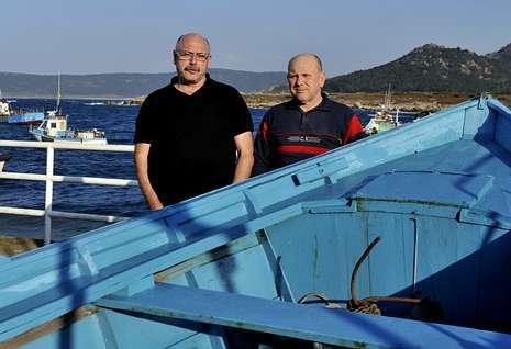 Antonio Mouzo y Manuel Rodr�guez, apoyados en una lancha en el puerto de su Camelle natal.