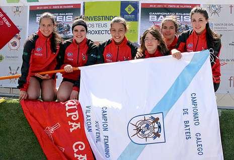 Las flamantes campeonas posan con la bandera conseguida en la mañana de ayer en Vilaxoán.