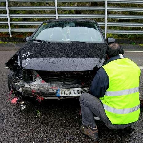El operario de la grúa que acudió a remolcarlo examina la parte frontal del coche en el que iban los cuatro heridos