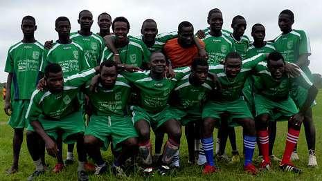 Jóvenes de la comunidad guineana forman con las camisetas y el material llegado desde Fisterra.